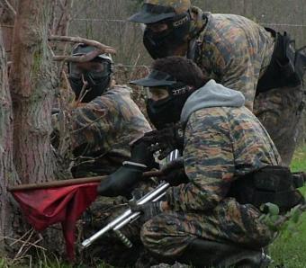 Teammates crouching down behind tree