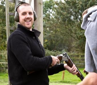 Happy stag party member shooting clay pigeons at our Bristol outdooor centre