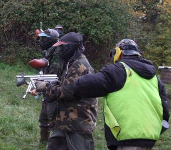 Instructor helping team members on paintball