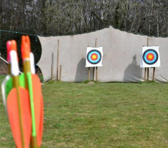Archery arrows and targets with net in the background