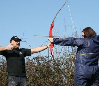 Archery instructor giving demonstration