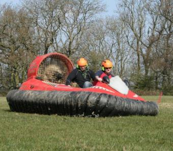 two lads on a stag do taking a corner in a hovercraft