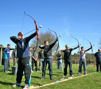 Clay archers in a row taking aim