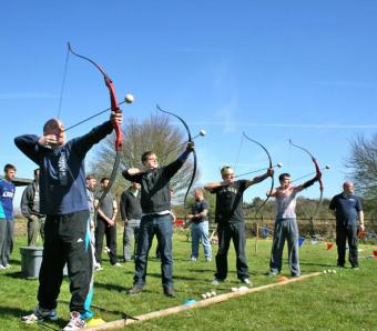 Stag do members taking aim with their bows and arrows on clay archery