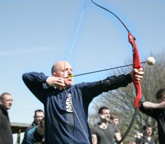 Clay archer pulling back and about to release arrow