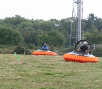 two hovercrafts being flown around a field at max events
