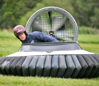 Two stag do member positioning his body for corner in Hovercraft