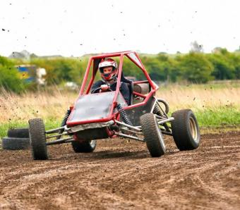 Kicking up some mud on the off road track in a Rage Buggy